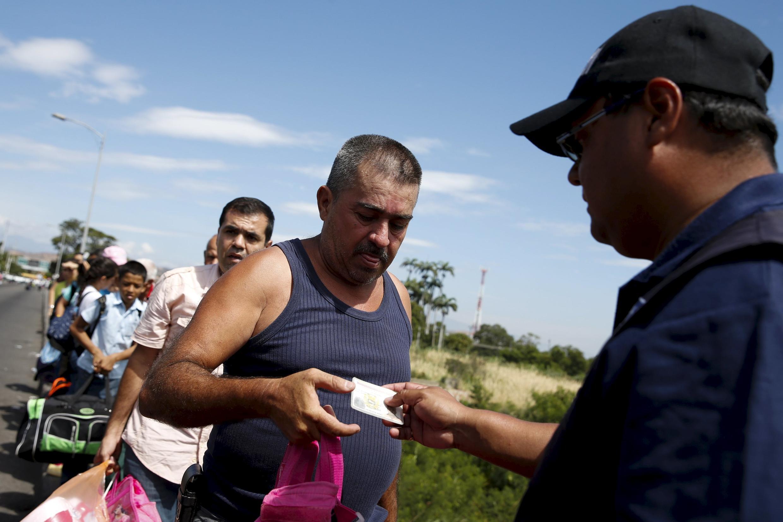 Un funcionario venezolano controla los documentos de la gente que cruza el puente Simón Bolívar hacia Colombia, este 26 de agosto de 2015.