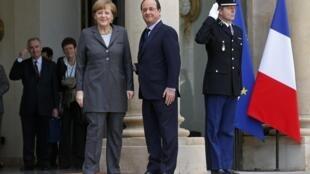 President François Hollande (R) welcomes Chancellor Angela Merkel to the Elysée