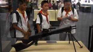 Des enfants chinois observent une arme utilisée par l'armée japonaise durant la Seconde Guerre mondiale, lors d'une exposition à Pékin, le 3 septembre 2014.