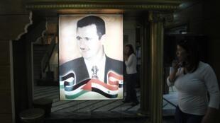 Retrato do presidente sírio Bashar Al-Assad dentro da sede do canal televisão oficial do país após ataque dos rebeldes ao local nesta segunda-feira.
