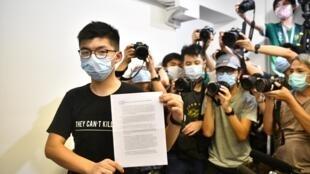 Le militant hongkongais pro-démocratie Joshua Wong montre sa lettre d'invalidaiton de candidature pour le les législatives locales, lors d'une conférence de presse le 31 juillet 2020.