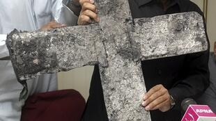Shahbaz Bhatti shows a cross which was burned during an attack on a church in Punjab in 2005