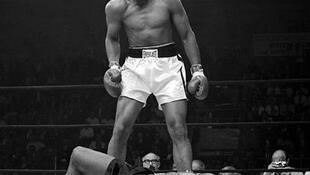 A 22 ans, le boxeur américain Cassius Clay, futur Mohamed Ali, bat le tenant du titre mondial des lourds Sonny Liston, au septième round, par KO.