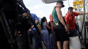 Des Brésiliens remplissent des bidons d'essence dans une station à Rio de Janeiro, sous l'oeil des policiers, le 28 mai 2018.