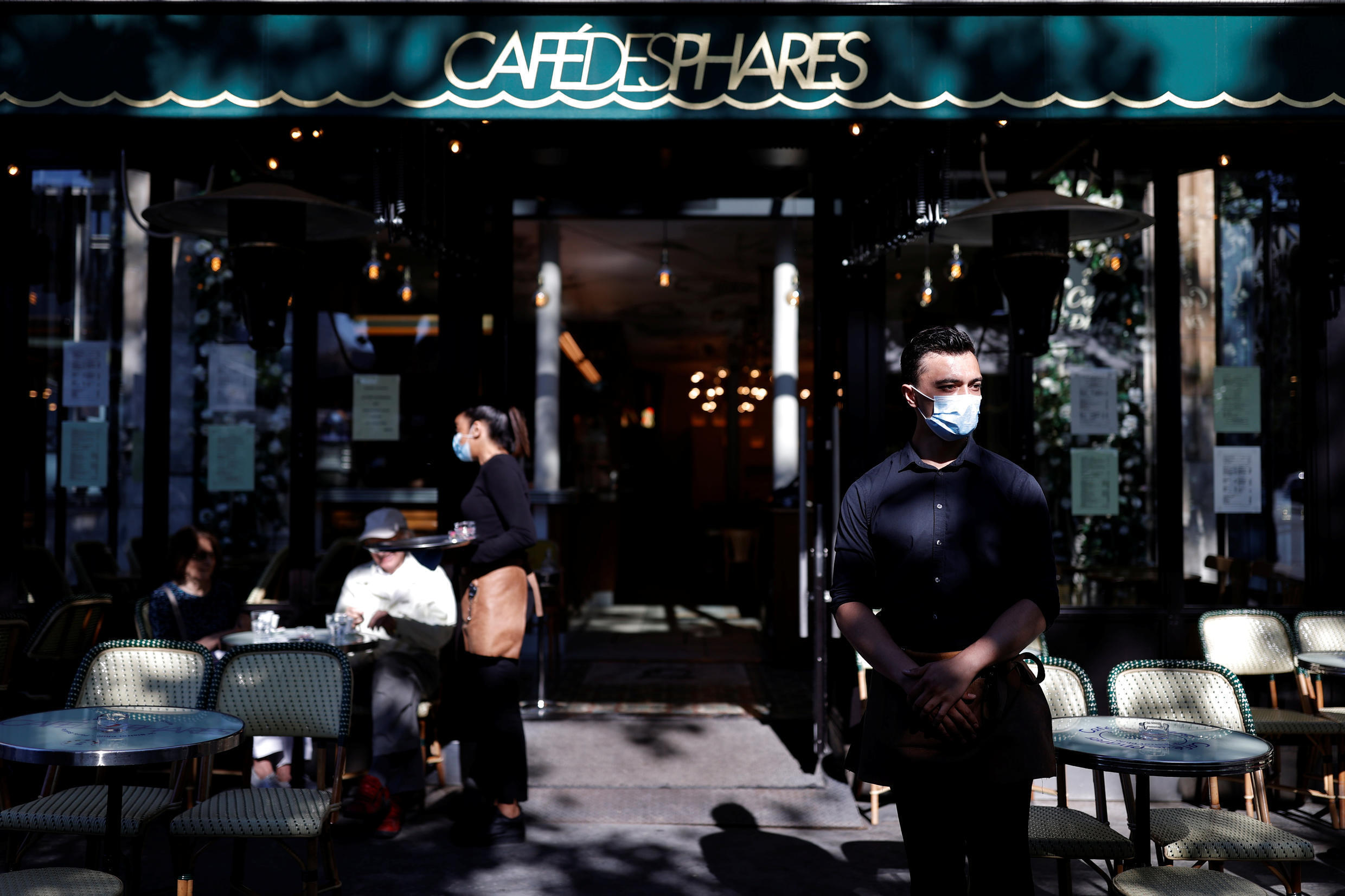 A waiter stands in front of Café des Phares, as restaurants and cafes reopen their terraces in Paris, which the government considers to be vulnerable to new Covid-19 infections.
