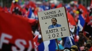 "A supporter of embattled Nicaraguan President Daniel Ortega holds a placard reading, ""Let's go to the Polls, (Ortega) Till 2021"" during a pro-government rally at which Ortega rejected early elections"