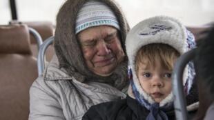 Una mujer con un niño huye en un autobus de Debaltseve, el 4 de febrero.