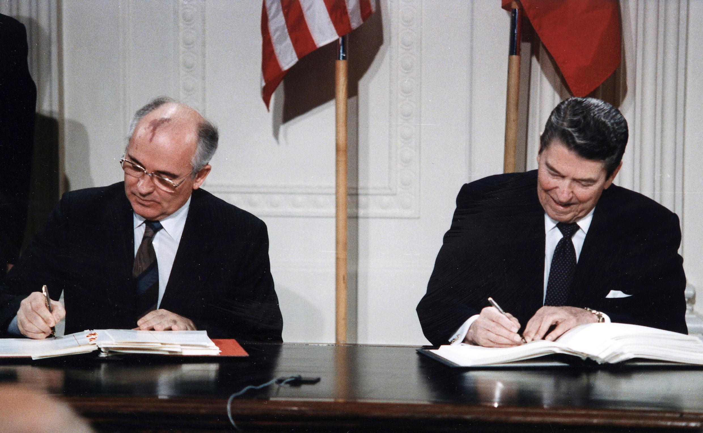 O Secretário Geral da União Soviética, Mikhail Gorbachev, e o presidente dos Estados Unidos, Ronald Reagan, assinam o Tratado de Forças Nucleares de Alcance Intermediário na Casa Branca, em 1987.