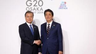 Le Président sud-coréen Moon Jae-in (gauche) et le Premier ministre japonais Shinzo Abe au sommet du G20 à Osaka le 28 juin 2019