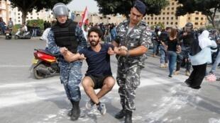 La policía arrastra a un manifestante durante una operación para abrir una carretera bloqueada durante las protestas antigubernamentales en Beirut.