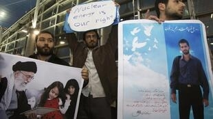 estudantes iranianos aguardam chegada da delegação da AIEA em Teerã com fotos de cientistas do programa nuclear assassinados misteriosamente nos últimos dois anos.