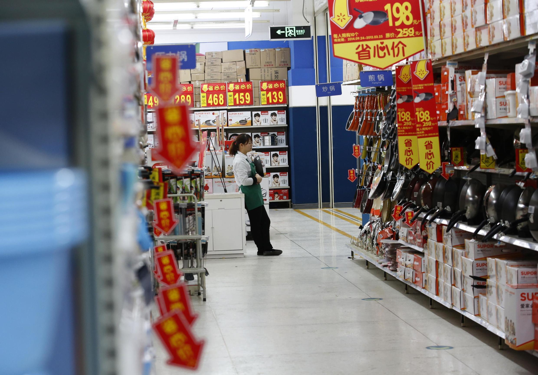 Một nhân viên bán hàng đang đợi khách trong một thương xá ở Bắc Kinh, 19/01/2015.
