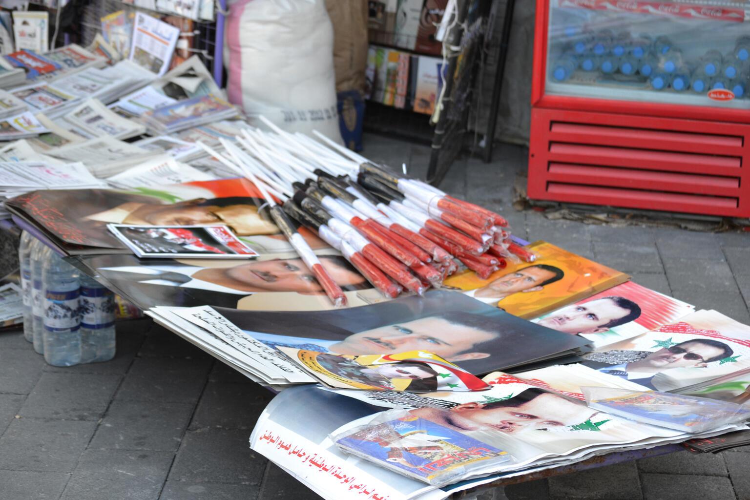 Des bouteilles d'eau, des journaux et différents portraits sont proposés à la vente sur le trottoir d'une rue fréquentée de Damas.