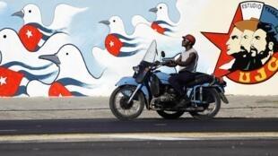 Un homme conduisant sa moto face à une peinture murale réalisée par l'Union des jeunes communistes, à La Havane, le 15 avril 2011.