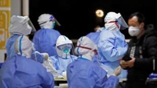 Personal sanitario con indumentaria protectora aguarda a hacer pruebas de detección del coronavirus al personal del aeropuerto de Pudong, el 22 de noviembre de 2020 en la ciudad china de Shanghai