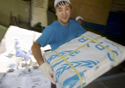 Employees unload humanitarian aid from a UNHCR plane at an airport in the city of Andizhan