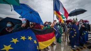 Des manifestants tiennent des drapeaux européens sur la passerelle des Deux-Rives, le pont qui relie la frontière française et allemande à Strasbourg le 14 juin 2020.