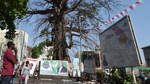 People walk past general election posters for Sierra Leone's presidential candidates on 3 March, 2018 in Freetown.