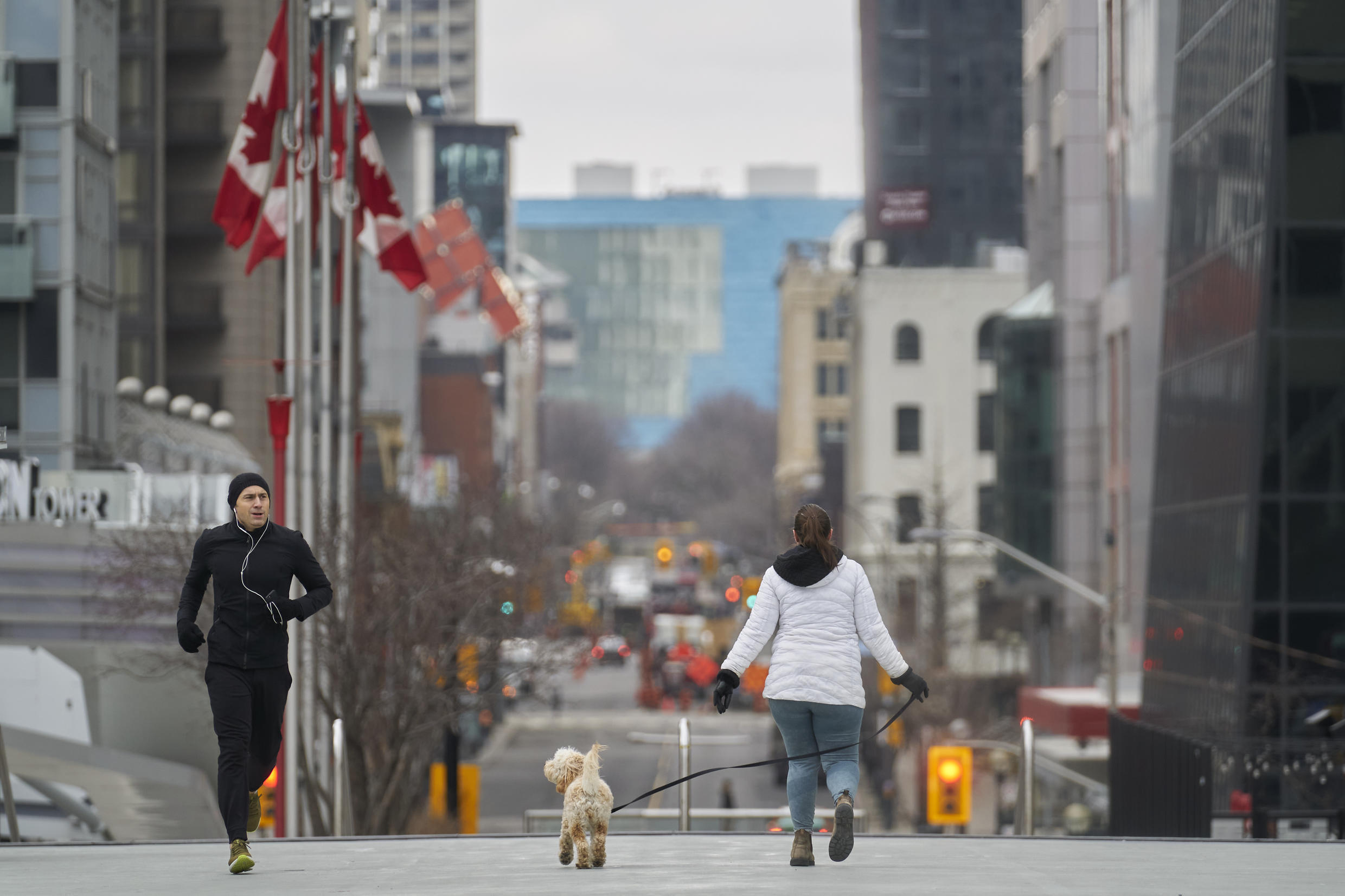 A jogger keeps his distance from a woman walking her dog in downtown Toronto, Ontario, while a Can$82 billion plan to aid Canadians cope with the economic impact of the coronavirus pandemic hit a snag in the Ottawa parliament