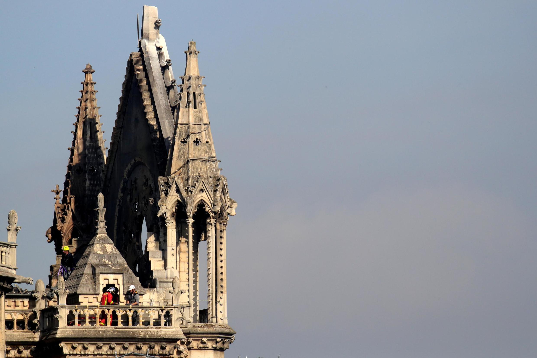 Homens trabalhando para fortalecer uma parte da Catedral de Notre-Dame