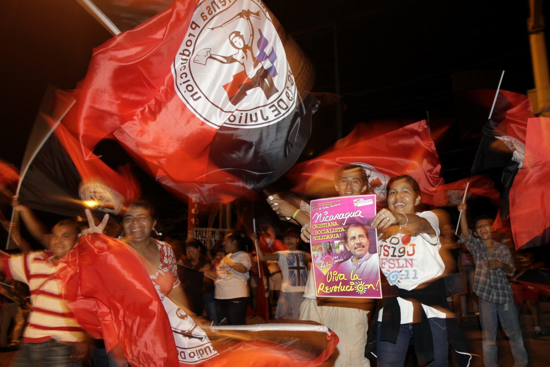 Managua, Nicaragua, le 6 novembre 2011. Des partisans du président sortant Daniel Ortega brandissent son portrait, en agitant des drapeaux du FNLS, à l'annonce des premiers résultats de la présidentielle.
