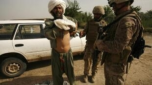 An Afghan man shows his scars to U. S Marines from Lima Company, 3rd Battalion, 6th Marines around the area of Karez-e-Sayyidi