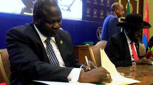 Le chef rebelle Riek Machar (G) et le président du Soudan du Sud, Salva Kiir signant l'accord de partage du pouvoir à Khartoum, au Soudan, le 5 août 2018.