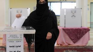 Une femme dépose son bulletin dans l'urne d'un bureau de vote de Jeddah, en Arabie saoudite.