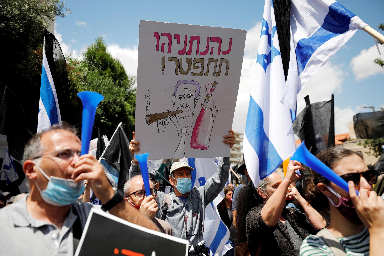 """Manifestantes en contra de Netanyahu, en la pancarta se puede leer en hebreo  """"Netanyahu dimite"""",  justo antes de que se abra su juicio por corrupción, fuera de su residencia en Jerusalén, 24 de mayo de 2020."""