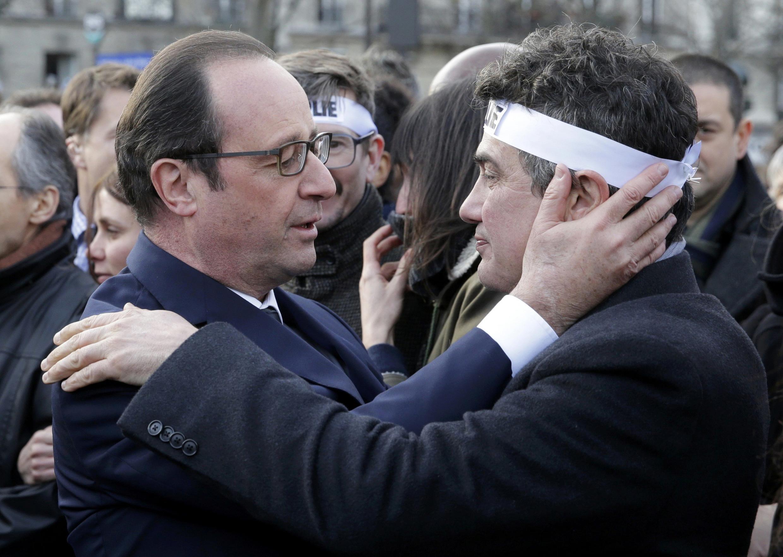 O presidente francês, François Hollande, abraça um dos colaboradores da revista Charlie Hebdo, Patrick Pelloux, durante a marcha contra o terrorismo em Paris, no dia 11 de janeiro.