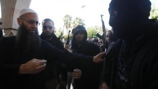 Le salafiste Ahmed al-Assir (G) demande à ce partisan d'ôter son masque.