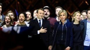 Emmanuel Macron cercado pela família na esplanada do Museu do Louvre.