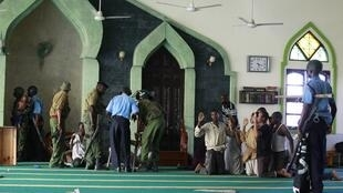Muslim men are detained by police officers at the Masjid Mussa mosque in Mombasa, 2 February, 2014
