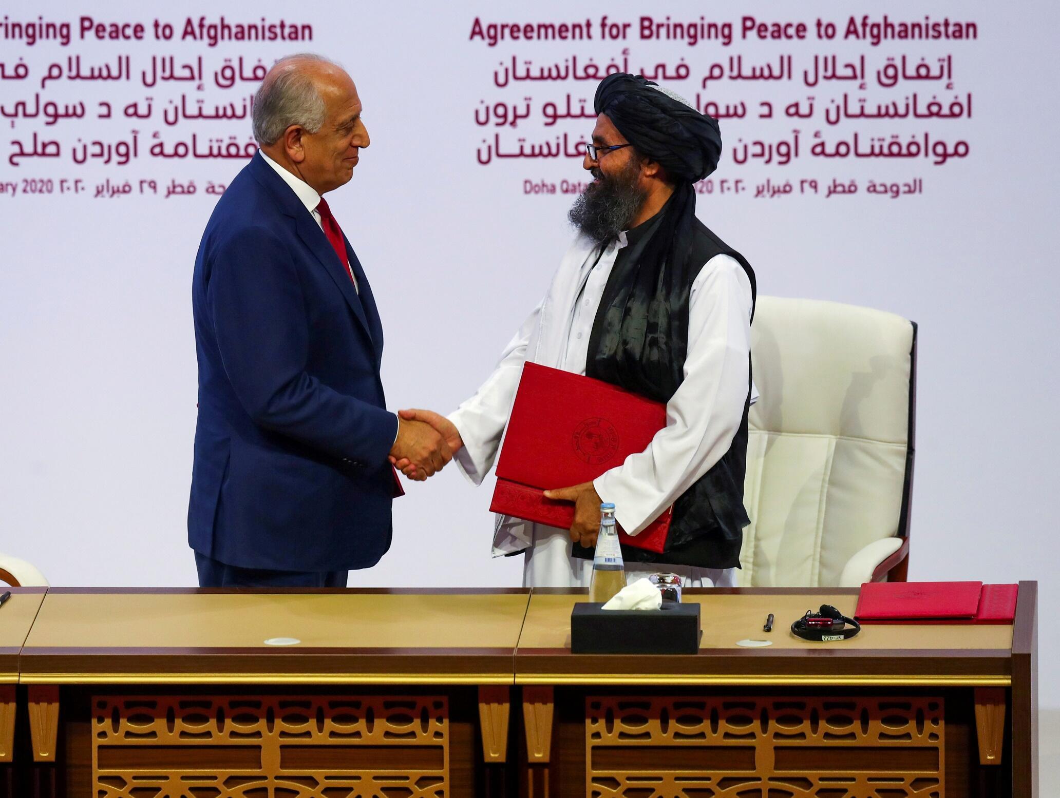 ملا عبدالغنی برادر، رئیس هیئت طالبان در گفتگوهای صلح دوحه، و زلمای خلیلزاد، نمایندۀ دولت آمریکا برای افغانستان پس از امضای توافق میان دو کشور