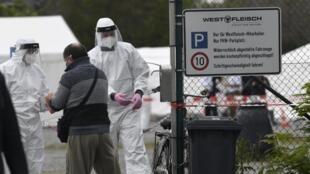 Um empregado da empresa de transformação de carne Westfleisch em Hamm, na Alemanha, desinfeta as mãos para realizar o teste do covid-19 em 10 mai de de 2020.