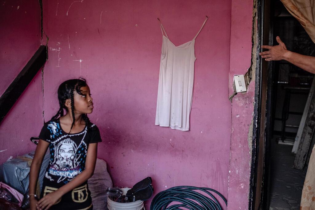 Angie, une jeune fille de l'une des rares familles qui vivent encore dans un immeuble en ruine, regarde une grande fissure dans le mur de son appartement dans un complexe de logements sociaux détériorés, sur les hauteurs de Petare.