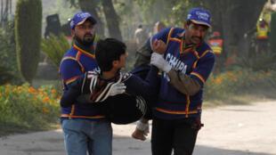 A Peshawar, un blessé est évacué par des secouristes après l'attaque d'une école revendiquée par les talibans du TTP, le 1er décembre 2017.