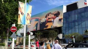 Jean-Paul Belmondo et Anna Karina s'embrassent au fronton du Palais des Festivals à Cannes.