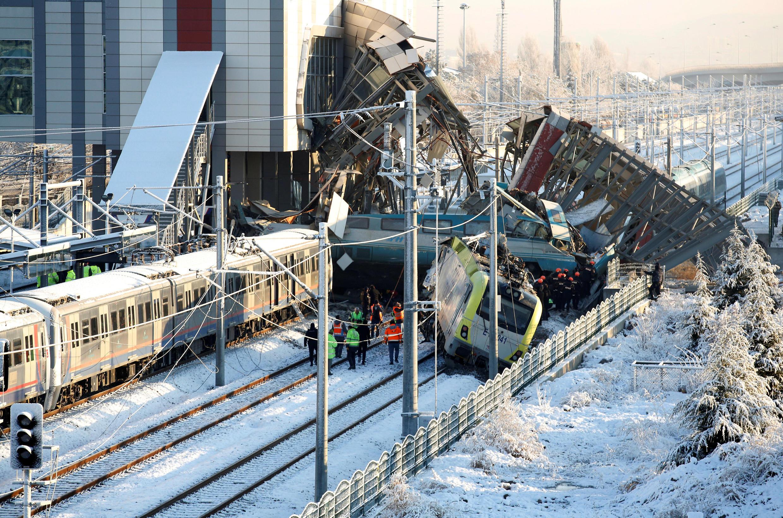 Des équipes de secours s'affairent autour des wagons blanc et bleu couverts de débris pour évacuer des corps. Une fine couche de neige recouvre les rails.