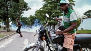 Muandamanaji wa DRC akiwa kwenye pikipiki akikabiliana na polisi wa kutuliza ghasia.