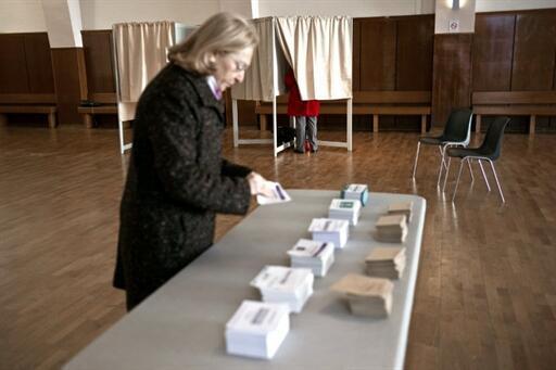 Một nữ cử tri tại Thành phố Dijon đang chọn phiếu bầu ngày 20/03/2011.