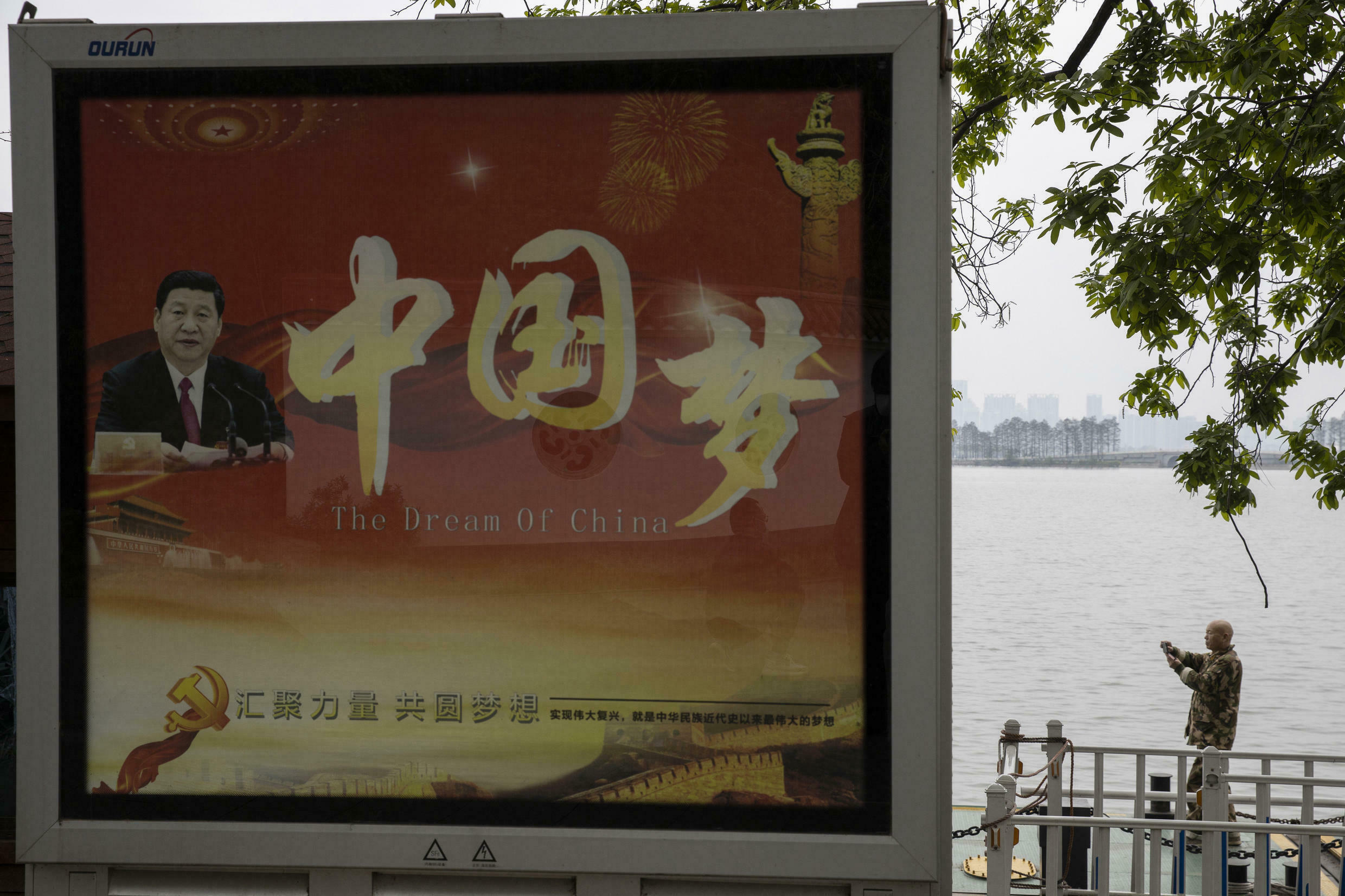 """A worker wearing a mask to reduce the chances of contracting the coronavirus takes a photo near a government propaganda poster showing Chinese President Xi and the words """"China Dream"""" at the East Lake park in Wuhan in central China's Hubei province on Thursday, April 2, 2020."""