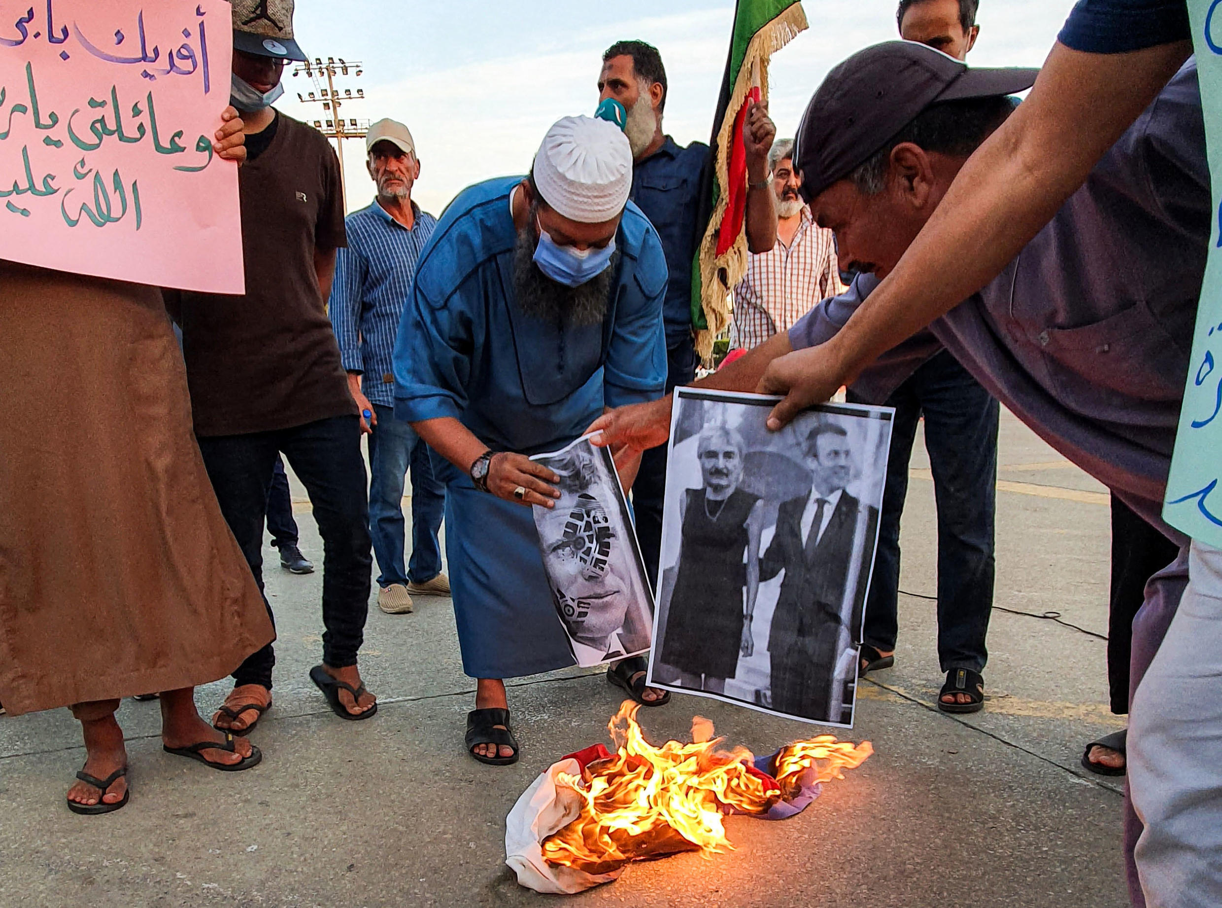 Demonstrators set fire to pictures of French President Emmanuel Macron in Libya