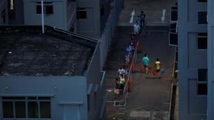 Des travailleurs migrants placés en quarantaine font la queue pour prendre leur petit-déjeuner, à Singapour, le 30 avril 2020.