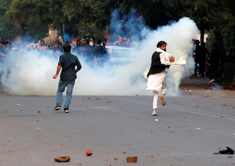 Des manifestants courent pour échapper au gaz lacrymogène tiré lors de la contestation contre la nouvelle loi sur la citoyenneté, à New Delhi, le 15 décembre 2019.