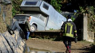 Un bombero cubierto de lodo se dirige hacia un vehículo en Casteldaccia, cerca de Palermo. Italia
