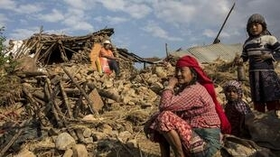 Uma nepalesa, sobre as ruínas da sua casa