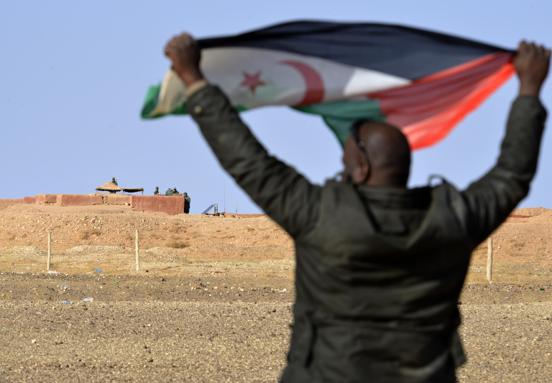 Un saharaui sostiene una bandera del Frente Polisario ante un puesto de soldados marroquíes en el muro de separación entre Sáhara Occidental y Marruecos, el 3 de febrero del año 2017 en la zona de Al Mahbes