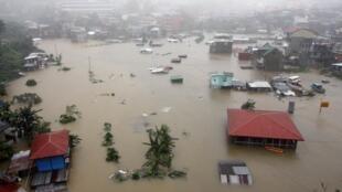 Dezenas de casas submersas pela enchente causada por tempestades tropicais no nordeste das Filipinas.