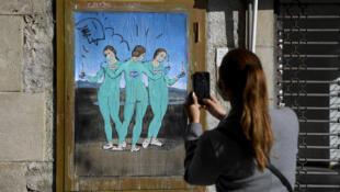 """Una mujer toma una foto de la obra del artista callejero italiano TvBoy llamada """"Las tres vacunas"""" que representa el cuadro Las tres gracias del pintor italiano Rafael, en Barcelona, España, el 19 de enero de 2021"""